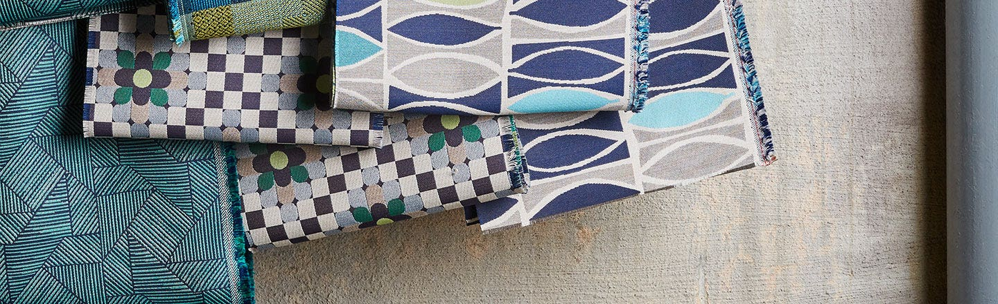 Blue and green patterned fabrics in a pile