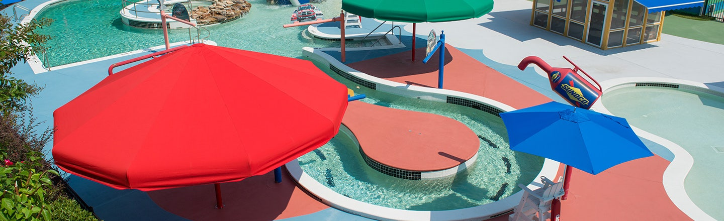 Red, green, and blue awnings near pool