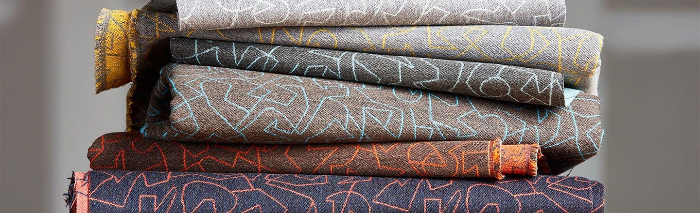 Stack of folded gray blue orange patterned fabrics